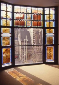 In 1990, the Friends commissioned a stained glass window (at the cost of £6,972) in multi coloured abstract design by Chinks Grylls for the extension built in 1989.  The design brief was to produce a window that both reflected the contents of this gallery and was interesting to people looking at the building from the outside.  It also had to work with the metalwork grill that the artist Alan Evans was designing for the outside of the building.  Chinks Grylls worked with a number of objects in the collection, including the only other piece of stained glass in the gallery.  The panel by Paul Woodroffe inspired the colours used in the final pieces.  Other inspirations came from rush seats, furniture inlay and painted decoration. The artist looks back on it as being an important first commission which helped steer her future direction as glass artist working with architecture.  She continues to work in the South West.